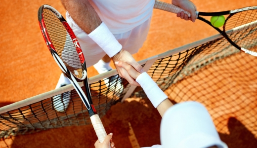 Two Tennis players shaking hands over the net after the match